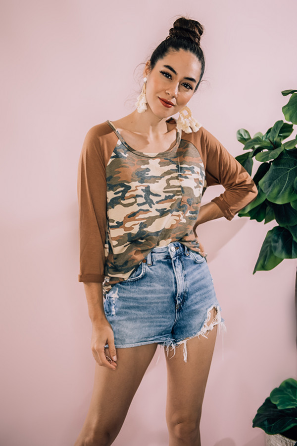 "MULTI CAMO PRINT RAGLAN TOP WITH RUST COLOR SLEEVES. MODEL INFO: PIPER – SIZE 0, 5'5"" WEARING A SMALL. NIKI – SIZE 14, 5'4"", WEARING A LARGE. 60% POLYESTER, 35% RAYON, 5% SPANDEX SMALL 0-4 MEDIUM 6-10 LARGE 12-14"