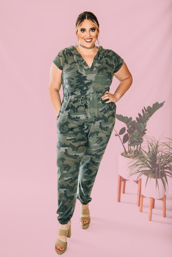 MADE IN USA. OVERSIZED SHORT SLEEVED CAMO JUMPER WITH ELASTIC ON ANKLES, TIE WAIST AND HOOD. AMANDA IS A SIZE 2, WEARING A SMALL. NIKI IS A SIZE 14, WEARING AN XL. XS 0-4 S 4-8 M 8-12 L 12-16 XL 16-18