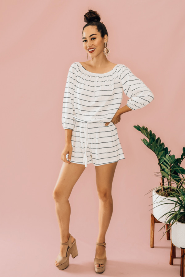 WHITE AND BLACK STRIPED ROMPER. OFF THE SHOULDER TOP, DRAWSTRING WAIST, LONG SLEEVE. 95% POLYESTER, 5% SPANDEX. PIPER IS 5'4 SIZE 0, WEARING SMALL AND NIKI IS A SIZE 14 WEARING AN XL XS 0-2 S 4-6 M 8-10 L 12-14 XL 14-16