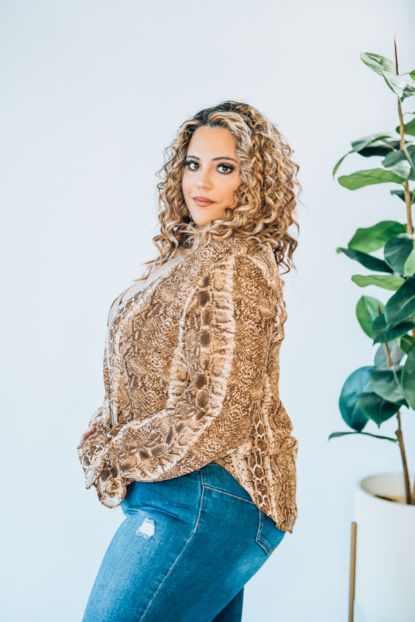 """SURPLICE TOP WITH CLASP, RUFFLE DETAIL AT SLEEVE. BROWN SNAKESKIN PRINT. MODEL INFO: STEPHANIE – SIZE 4, 5'1"""", WEARING A SMALL. NIKI – SIZE 14, 5'4"""", WEARING XL - SNUG FIT 100% POLYESTER  X-SMALL 0-2 SMALL 4-6 MEDIUM 6-8 LARGE 10-12 X-LARGE 12-14"""