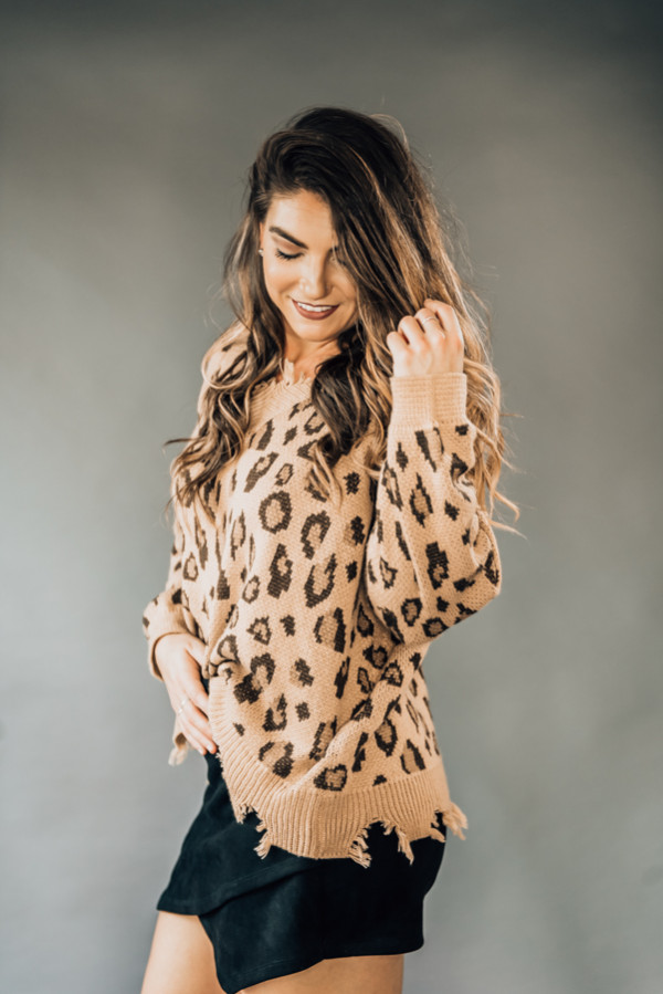 """TAN AND BROWN LEOPARD PRINT SWEATER WITH DISTRESSED FINGE DETAIL AT NECK AND BOTTOM. MODEL INFO: SISSY - SIZE 6, 5'6"""", WEARING A SMALL. 100% ACRYLIC SMALL 2-6 MEDIUM 6-12 LARGE 12-16"""