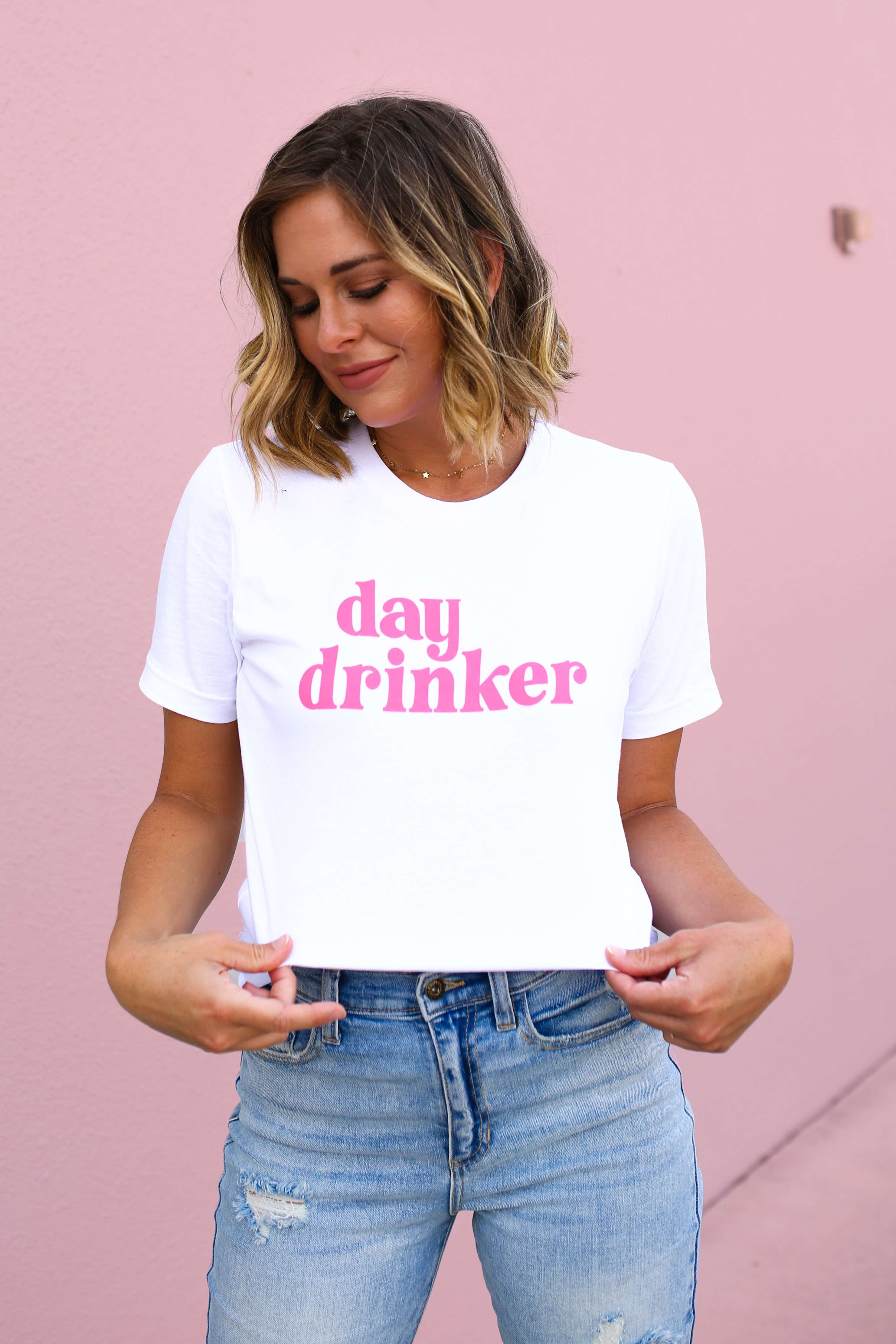 """MAVERICK EXCLUSIVE! WHITE UNISEX TEE. NEON PINK """"DAY DRINKER"""" GRAPHIC. 100% COTTON. GABBY IS 5'8"""" A SIZE 12 AND 38DD WEARING A LARGE. AMANDA IS 5'7"""" A SIZE 2, WEARING A SMALL. S 0-4 M 4-8 L 8-12 XL 12-16 XXL 16-18"""
