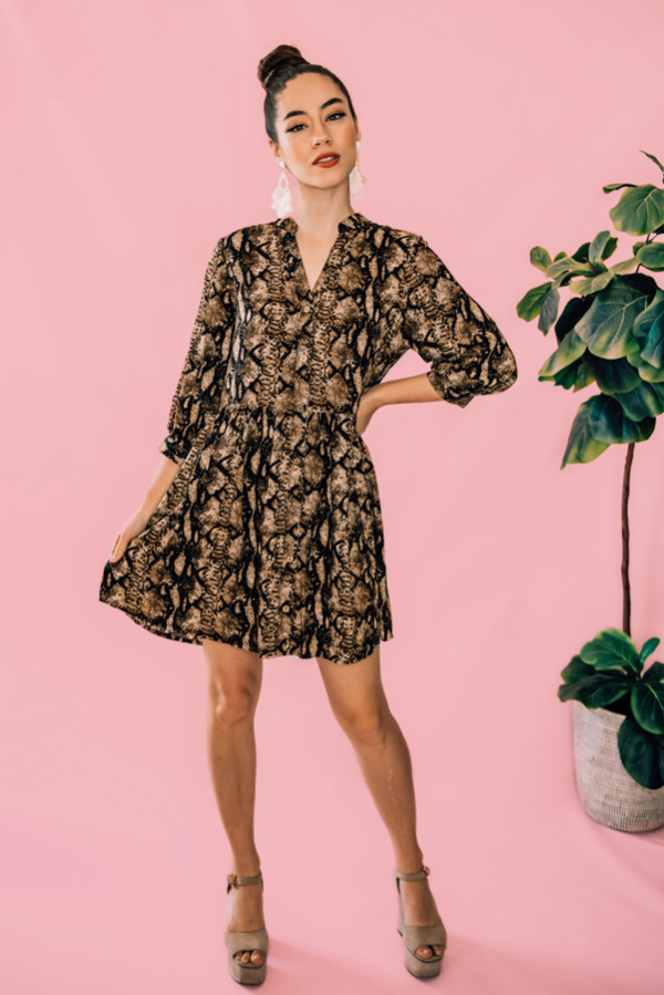 BLACK, BROWN, AND CREAM-COLORED SNAKE PRINT TUNIC. BUTTON UP AND V-NECK. ELBOW LENGTH SLEEVES. 95% POLYESTER, 5% SPANDEX. PIPER IS 5'4, SIZE 0 WEARING A SMALL.  XS 0-2 S  4-6 M  8-10 L 12-14 XL 14-16