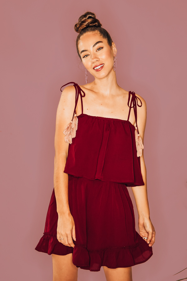 BURGUNDY, LAYERED, ROMPER WITH PINK TASSLE TIE STRAPS. 100% POLYESTER. PIPER IS 5'4 SIZE 0, WEARING SMALL, STEPHANIE IS A SIZE 4, WEARINGS A SMALL  NIKI IS A SIZE 14 WEARING AN XLARGE.  XS 0-2 S 4-6 M 8-10 L 12-14 XL 14-16
