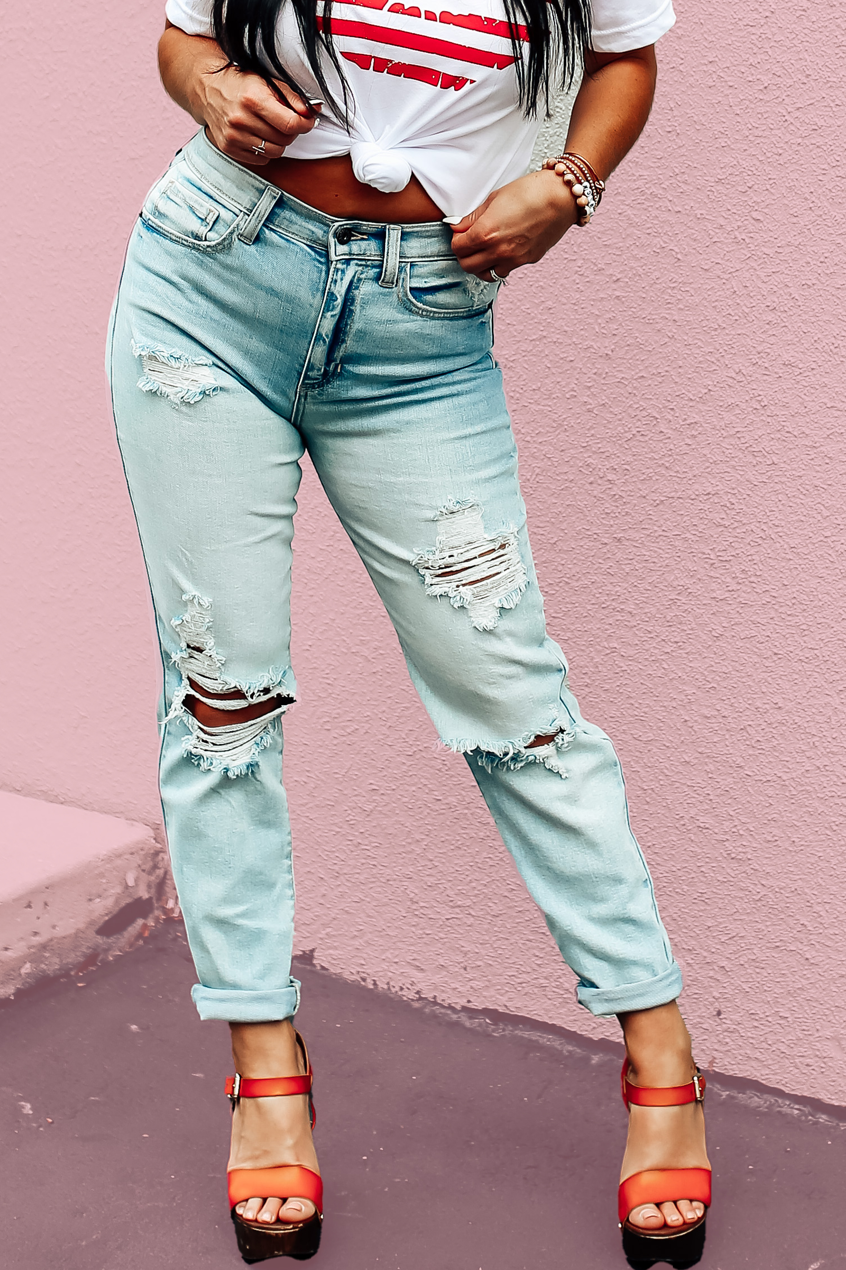 """PREMIUM DENIM IN A LIGHT WASH. LOTS OF DISTRESSING. LOOSE, BOYFRIEND STYLE FIT. 29 IN. INSEAM. 99% COTTON, 1% SPANDEX. AMANDA IS 5'7"""" A SIZE 2, WEARING A 26. STEPHANIE IS 5'4"""" SIZE 4 WEARING A 26."""