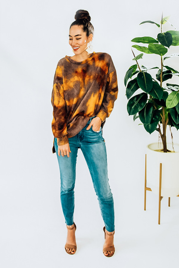 BROWN TIE DYE, HIGH-LOW, LONG SLEEVE KNIT TOP. ROUND NECK AND SLITS AT SIDES. FLEECE LIKE MATERIAL. PIPER IS A SIZE 0 AND WEARING A SMALL. NIKI IS A SIZE 14 AND WEARING AN X-LARGE. 95% POLYESTER 5% SPANDEX SMALL 4-6 MEDIUM 6-8 LARGE 8-10 X-LARGE 10-14